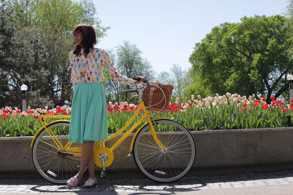 girl standing with bike in front of tulips